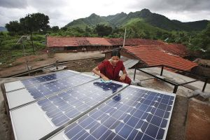 Den indiske barfotingeniøren Meenakshi Dewan sjekker solcellepanelet på et tak i landsbyen Tingnaput. (Foto: Abbie Trayler-Smith/ UK Departement for International Developement/ Flickr/